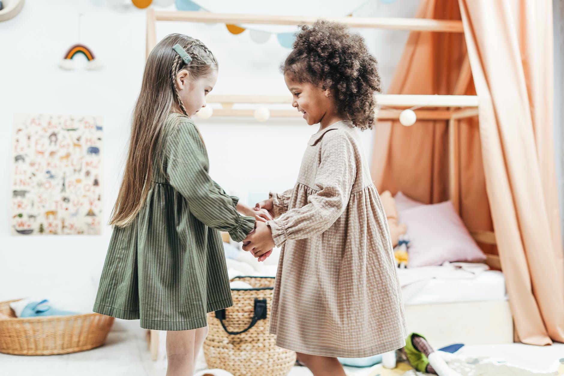 photo of girls wearing dress while holding hands